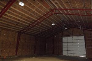 <p>Interior of equipment shed, farm building with 16x14 foot overhead door.</p>