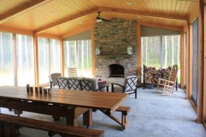 Outdoor eating and gathering place around screened in fireplace. (10 of 37)