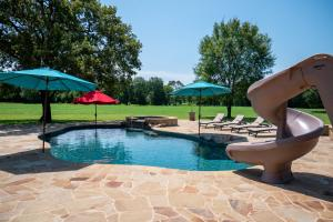 The owners thoughtfully planned out this pool build. Featuring a hot tub with spill over waterfall, jumping rock and an awesome slide for the kids!  (22 of 30)
