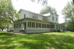 <p>Back side of large house showing large wrap arround sun porch.</p>